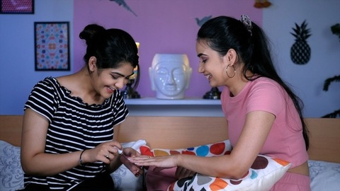 An Indian girl wearing a black printed T-shirt applying nail polish on her best friend's hand