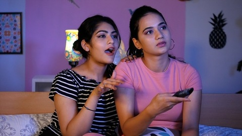Pretty sisters in casual clothes watching their favorite program on television