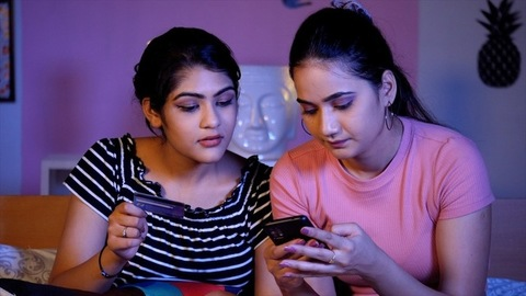 Cheerful girl helping her best friend in online shopping - e-commerce purchase