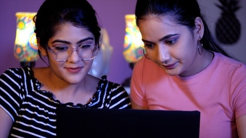 Pretty Indian sisters sitting on the bed at home using a laptop together