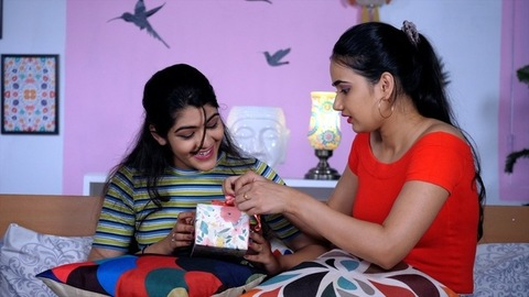 Cheerful female helping her elder sister to pack a gift - Birthday gift