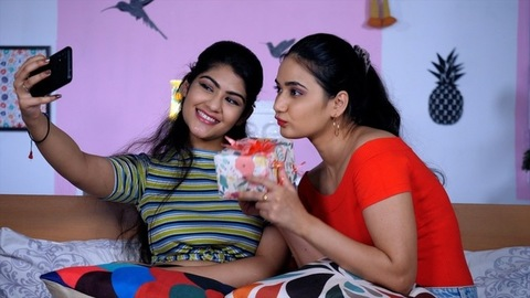 Pretty college-going students clicking a selfie using a smartphone at home