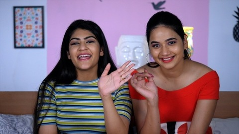 Happy young girlfriends waving their hands while talking to their relatives on a video call