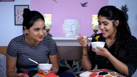Cheerful Indian sisters eating freshly prepared noodles in a ceramic bowl