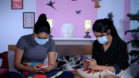 Teenage girls wearing blue medical masks scrolling / browsing on their smartphones - COVID protocol