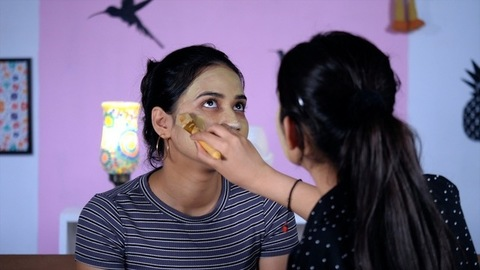 Beautiful teenage girl putting a face pack on her friend's face before going out