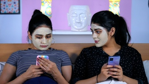 College-going students with face masks surfing the internet on their smartphones