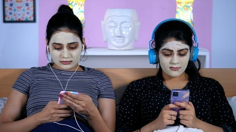 Best friends with face masks enjoying listening to music on their smartphones