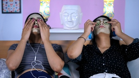 Indian sisters wearing jeans and a top putting cucumber slices in their eyes