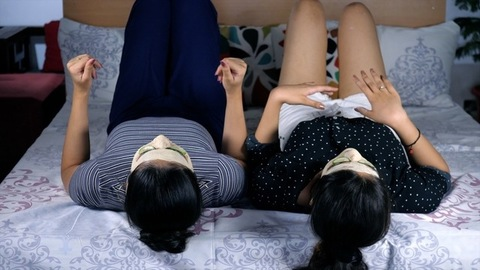 Beautiful girls with face packs singing and dancing on the bed enjoying together