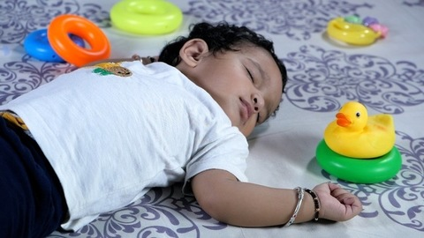 An adorable girl child wearing a white T-shirt sleeping on a comfortable bed