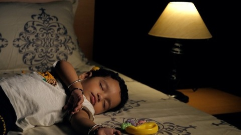A newborn baby girl wearing a white T-shirt sleeping peacefully with a nightlamp