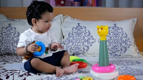 Cute Indian baby girl with black hair playing with colorful plastic toys in her leisure time
