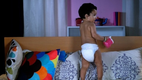 Cute bare-chested baby in diapers playing with her soft toys while sitting on a bed