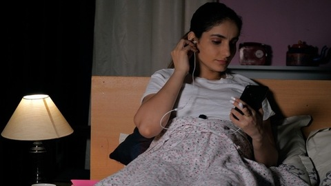 A young woman listening to good music on her smartphone at night in a dark room