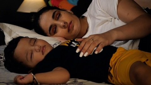 Tired Indian mother sleeping together with her sweet little girl child in the bedroom