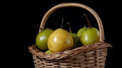 A heap of green and golden pears / Naak kept together in a bamboo basket