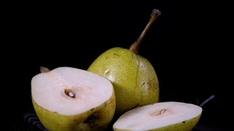 Whole and half green pears / Naak kept together on a black designer plate