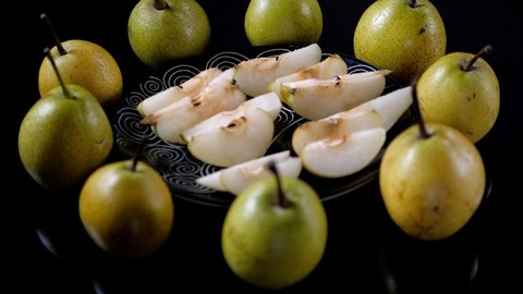 Pan shot of tasty and crunchy green pears cut in half served on a designer plate