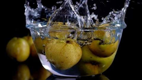 Golden yellow pears / Naak falling in a transparent bowl full of water with bubbles