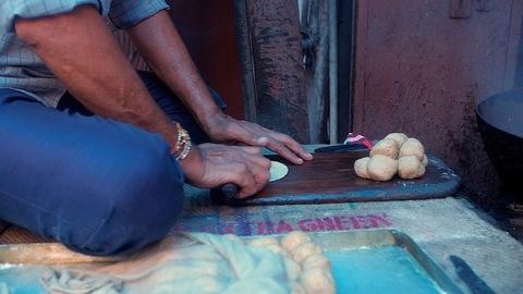 A vendor in a roadside restaurant in the process of making Pooris