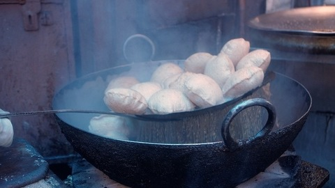 A worker in a roadside Dhaba deep-frying Pooris in a pan with hot oil