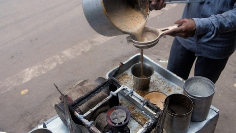 A local tea seller at a small shop serving freshly made tea in a big steel glass