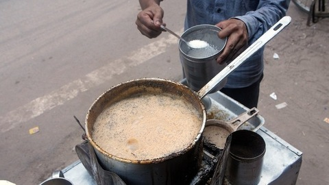 A local tea seller in a blue shirt adding a spoonful of sugar to freshly made tea - Indian Chai