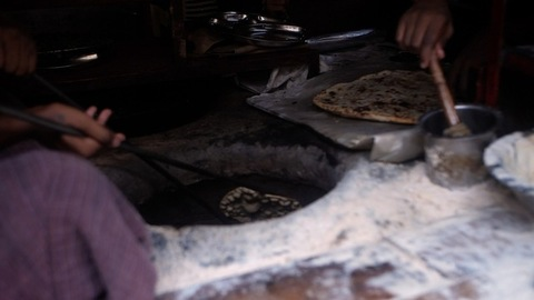A worker in a small restaurant making Parathas inside a tandoor