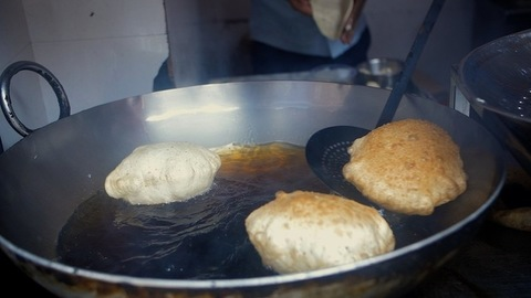 A worker in a small restaurant deep-frying Bature in hot oil