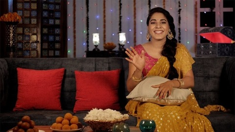 Traditionally dressed woman waving and chatting on a video call during Diwali