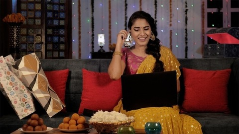 Pretty lady in a Sari showing her Diwali gift while chatting on a video call