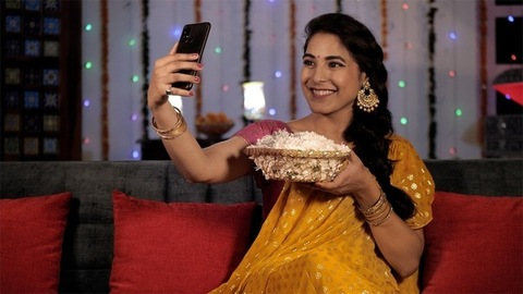 An attractive woman in a Sari clicking a selfie using her mobile - Indian festival