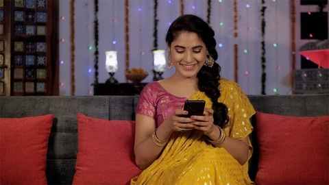 Cheerful lady in a Sari using her smartphone during the Diwali festival