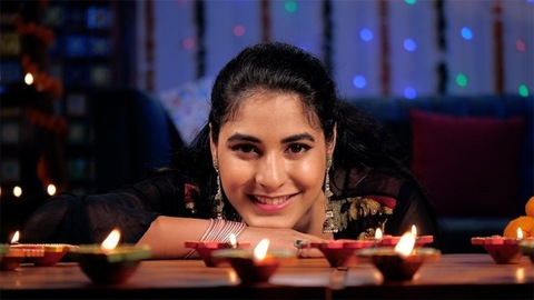 Young girl in her twenties watching Diyas burning brightly - Deepavali celebrations