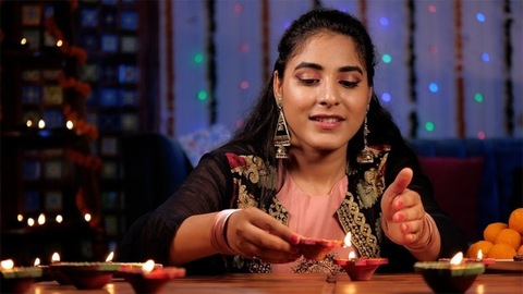 A beautiful Hindu girl lighting wax Diyas during the Deepavali festival