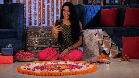 Cheerful girl talking on a video call while sitting near a traditional Rangoli