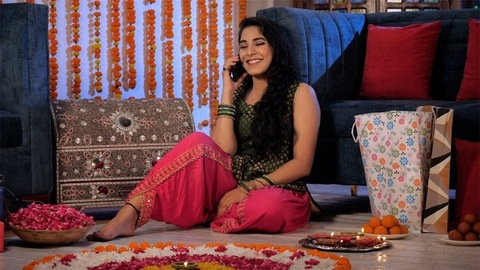 Young Indian female laughing while talking on a mobile with a festive background
