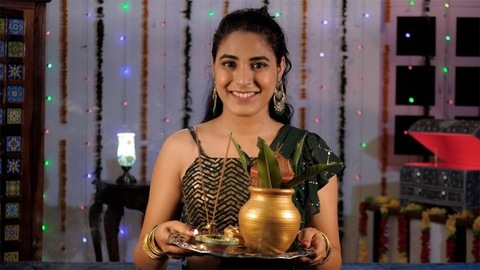An attractive lady holding a Puja Thaali with a Kalash on the occasion of Diwali