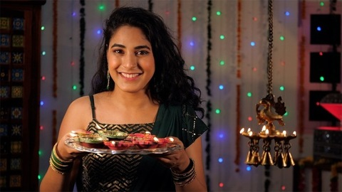 A cheerful woman standing with a plate of clay Diyas while celebrating Diwali