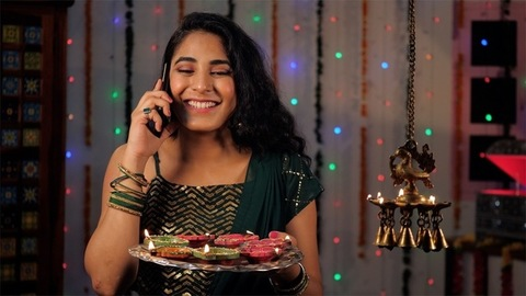 A young girl wishing her family and friends while talking on the phone during Diwali