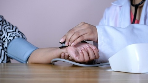 Professional lady doctor checking the blood pressure of a patient in the clinic