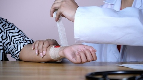 A medical nurse putting a white bandage on a wound of a young patient