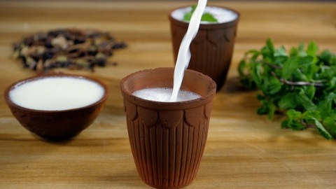 Buttermilk / Chaas pouring in a glass made of clay - a beautiful crockery