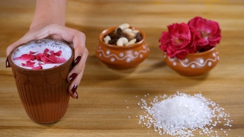 A lady serving a glass of chilled Chaas decorated with rose petals