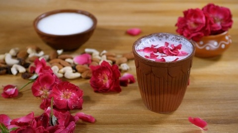 Beautiful red rose and its petals on a wooden table - Rose milk