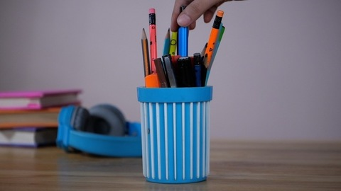 Pen stand with colored pens and pencils - A student taking a pen from a pen holder to write her notes