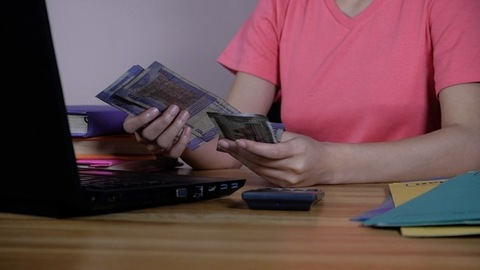 A female accountant using a calculator to calculate the household expenses