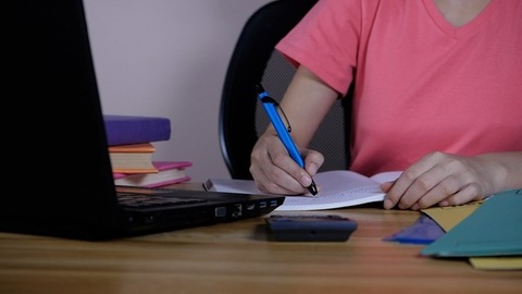 A young girl wearing a pink T-shirt using a laptop while doing research at home