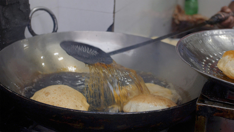 A man frying pooris in a huge deep cooking pot and collecting the freshly cooked ones in a tray